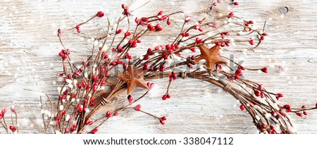 Christmas wreath with red and white berries and rusty metal stars on wooden background. Narrow format for web design. Falling snow effect. Vintage Style - stock photo