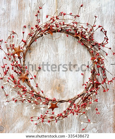 Christmas wreath with red and white berries and rusty metal stars on wooden background. Vintage Style. Toned image - stock photo