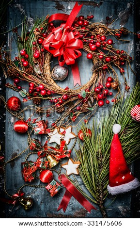 Christmas wreath with red holiday decorations and Santa hat on blue rustic wooden background, top view. - stock photo