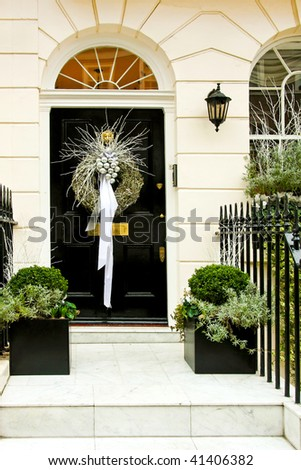 Christmas wreath with silver pendants at door - stock photo