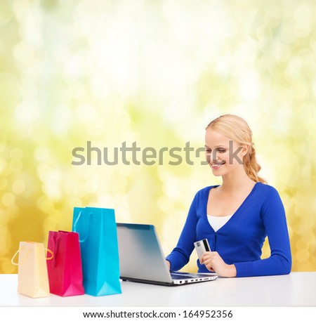 christmas, x-mas and online shopping concept - smiling woman with shopping bags, laptop and credit card - stock photo