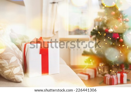 christmas, x-mas, holidays, winter and happiness concept - gift box on coach at home - stock photo