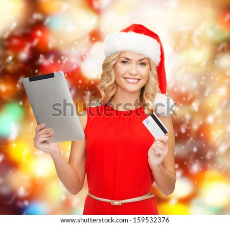 christmas, x-mas, online shopping concept - woman in santa helper hat with tablet pc computer and credit card - stock photo