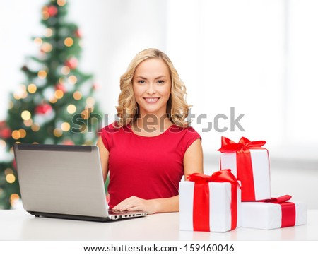 christmas, x-mas, online shopping concept - woman with gift boxes and laptop computer - stock photo