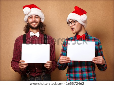 Christmas, x-mas, people, advertisement, sale concept - happy two man in santa helper hat with blank white board. Hipster style. - stock photo