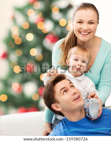 christmas, x-mas, winter, family, people, happiness concept - happy parents playing with adorable baby - stock photo
