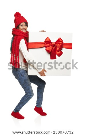 Christmas, x-mas, winter gift concept. Funny image of excited woman in sweater and hat carrying huge heavy gift box, in full length, isolated on white - stock photo