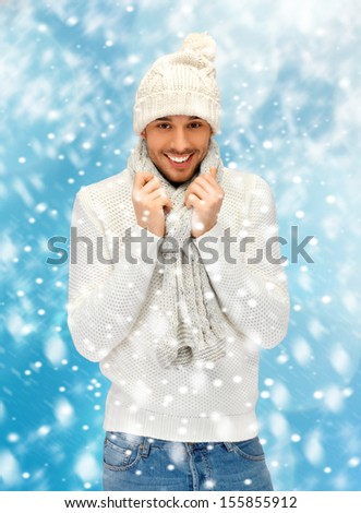 christmas, x-mas, winter, happiness concept - handsome man in warm sweater, hat and scarf