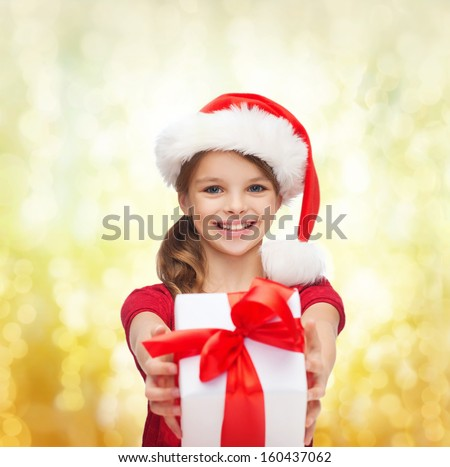 christmas, x-mas, winter, happiness concept - smiling girl in santa helper hat with gift box - stock photo