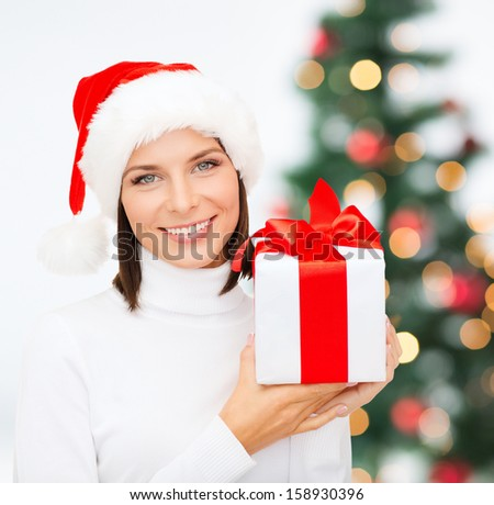 christmas, x-mas, winter, happiness concept - smiling woman in santa helper hat with gift box - stock photo