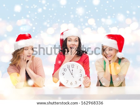 christmas, x-mas, winter, happiness concept - three smiling women in santa helper hats with clock showing 12 - stock photo