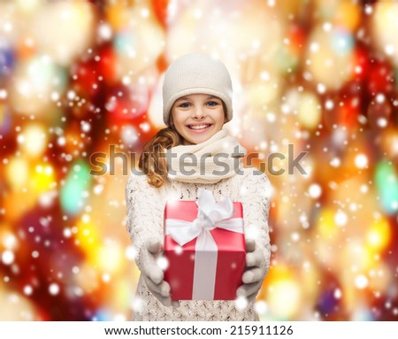 christmas, xmas, happiness concept - smiling girl in hat, muffler and gloves with gift box - stock photo