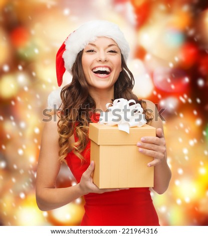 christmas, xmas, new year, happiness concept - laughing asian woman in santa helper hat with gift box - stock photo