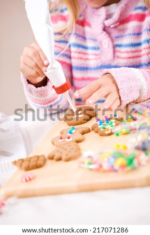 Christmas: Young Girl Using Icing To Decorate Cookies - stock photo