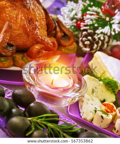 Christmastime banquet, festive table setting with bright candle light, New Year eve, tasty baked chicken, black olives, pine cone with snow decoration - stock photo