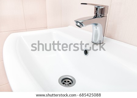 chrome faucet in the ceramic wash basin in the bathroom with a beige tile  on wall. Chrome Faucet Ceramic Wash Basin Bathroom Stock Photo 685425088