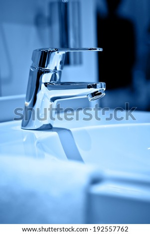 Chrome faucet with wash basin in blue tone - stock photo