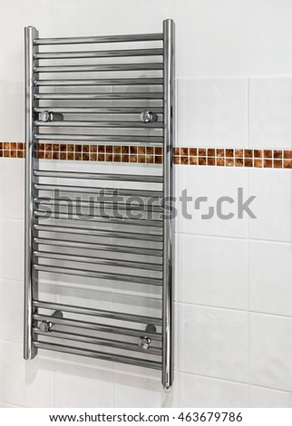 Chrome heated towel rail which serves a dual purpose as a radiator and towel dryer in modern bathrooms.