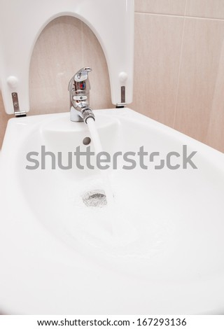 Chrome mixer tap with water in a bathroom.  - stock photo