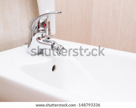 Chrome mixer tap with water in a bathroom. The photo is taken in horizontal composition. - stock photo