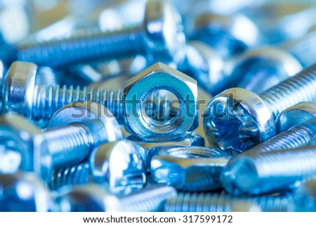 Chrome nuts and bolts close-up in blue tone - stock photo