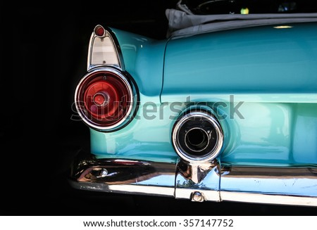 Chrome rear tail lights, bumper and exhaust of convertible turquoise Thunderbird vintage car. - stock photo
