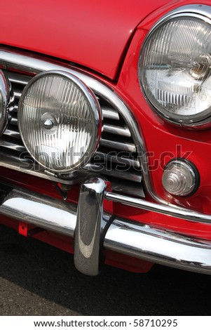 Chromed grille , bumper and twin headlamps of classic red rally car - stock photo