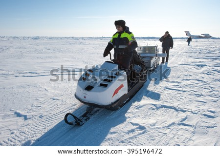 Chukotka, Russia - April 28, 2011: A member of the polar station in the North Arctic Ocean operates a snowmobile on a temporary runway drifting ice floe. Bright sunny day, the vast expanse of snow.