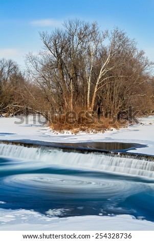 Chunks of ice swirl in the currents of the Big Blue River as water cascades over an old grist mill dam in Edinburgh, Indiana. - stock photo