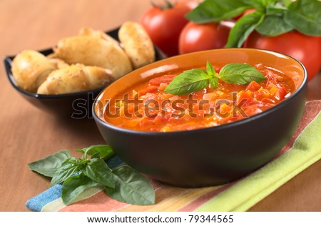 Chunky tomato soup made of tomatoes, carrots and onions and garnished with a basil leaf (Selective Focus, Focus on the basil leaf on the soup) - stock photo