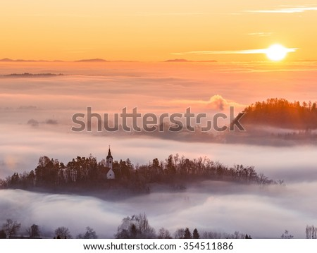 Church and castle hiding in the early morning fog. A misty sunrise in the countryside. - stock photo