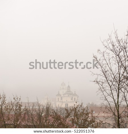 Church and roof of buildings in fog, view from hill, Vilnius, Lithuania