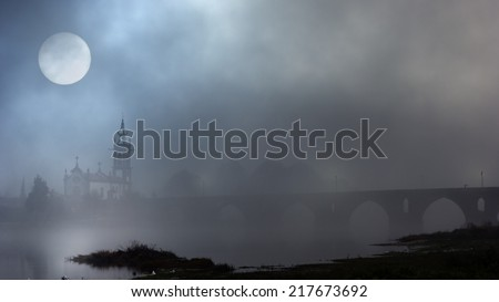 Church and stone bridge of medieval city of Ponte de Lima, north of Portugal in a foggy night or late evening. Added some digital noise. - stock photo