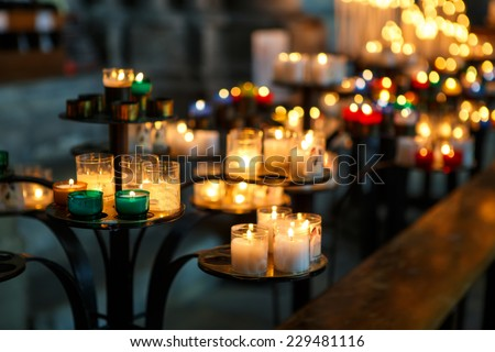 Church candles in red, green, blue and yellow transparent chandeliers - stock photo