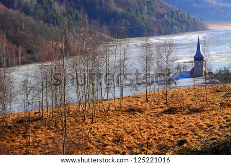 Church covered by polluted mud from a copper mine, lake Geamana, Romania - stock photo