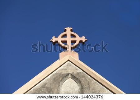 Church cross against plain blue sky - stock photo