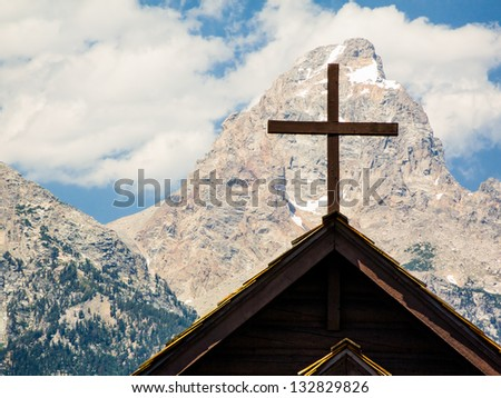 Church cross with mountain peak behind. Grand Teton National Park, Wyoming, USA. - stock photo