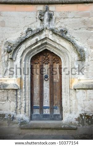 Church doorway with carved wooden door panel and decorative stonework - stock photo