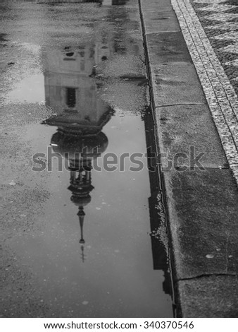 church in prague reflecting in a puddle on the street