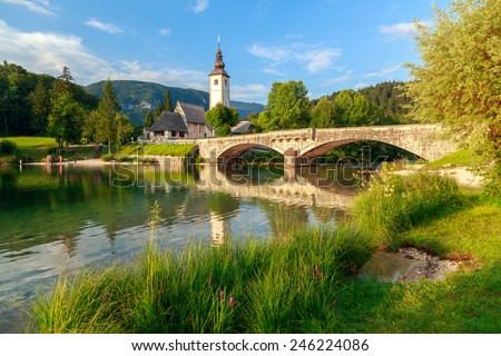 Church of Sv. John the Baptist and a bridge by the Bohinj lake, Slovenia - stock photo