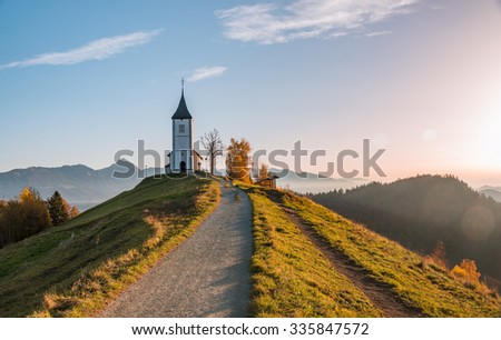 Church on the hill at sunrise. Beautiful scenery at Jamnik, Slovenia. Panoramic view of the mountains behind the church in the early morning. - stock photo