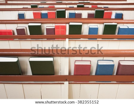 Church pews with various religious books - stock photo