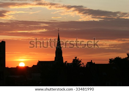 church silhouette on red and orange summer sunset with clouds - stock photo