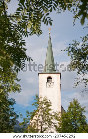 church spire against the cloudy sky surrounded by a tree - stock photo