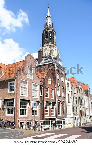 Church tower and historic houses in Delft, Holland