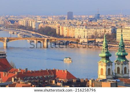 Church towers and Margaret bridge across Danube river, Budapest, Hungary - stock photo