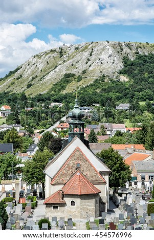 Church with cemetery and Braunsberg hill, Hainburg an der Donau, Austria. Religious architecture. Cultural heritage. Vertical composition. Beautiful place. - stock photo