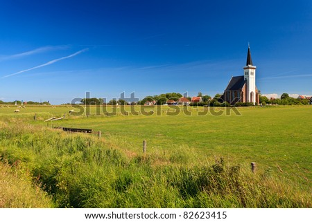 Church with grassland on a sunny day in spring - stock photo