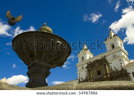 Church with pigeon flying on fountain and blue skies, shot at historical center of Quito, the capital of Ecuador - stock photo