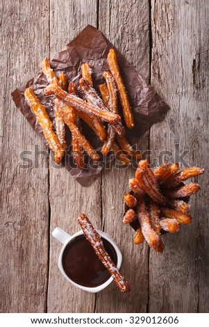 churros and hot chocolate on the table. vertical top view